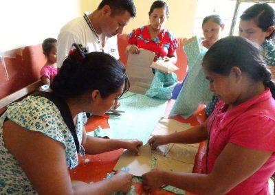 Mujeres capacitándose en técnicas de corte y confección