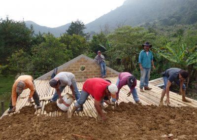 Aplicando lodo con paja en el tapanco de la casa ecológica